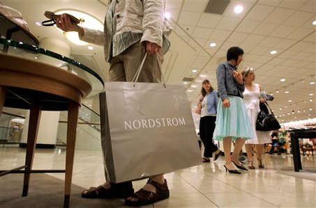 A shopper looks over a shoe display as others walk past in the women's shoe department of the downtown Seattle Nordstrom store, Wednesday, May 17, 2006. Nordstrom Inc. releases first-quarter earnings. (AP Photo/Elaine Thompson)